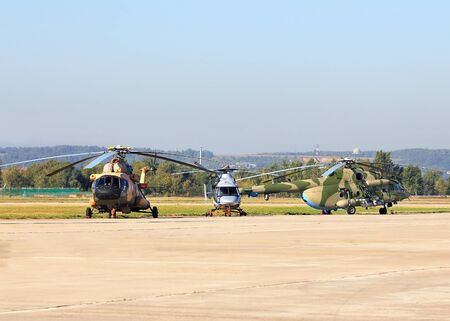 airfield: Three russian military transport helicopters at the air base airfield