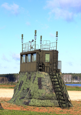 Camouflaged field command, communication and observation point with radio communication equipment at the training camp