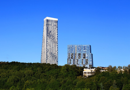 Two high modern houses on a hill covered with trees