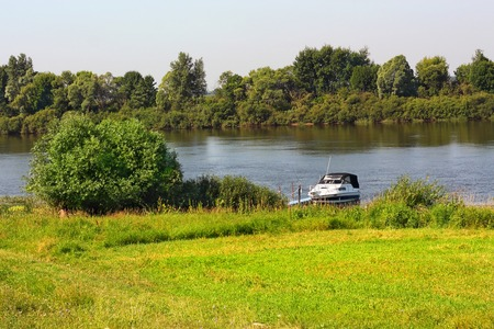 riverside landscape: Rural landscape with the view of small motorboat on the riverside Stock Photo