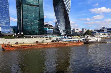 complex navigation: Barge and tugboat on the background of the waterfront and cityscape