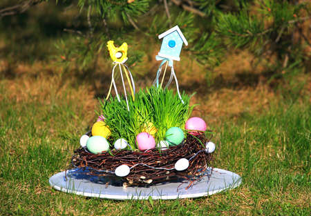 Wicker basket of twigs with Easter eggs with decorations of different colors on the green grass