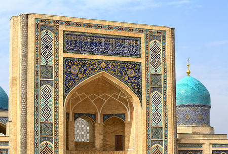 Old-time central asian styled wall of pishtak with pointed arche and persian paintings Stock Photo