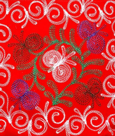 White, green and purple patterns on textiles of red color