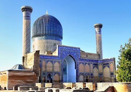 Medieval Central Asian mausoleum with oriental ornament, blue dome and decorative columns on the sides Stock Photo