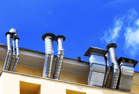 Ventilation pipes and actuators on the roof of building Stock Photo