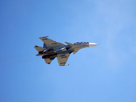 Modern russian fighter flying in a blue sky, bottom view Stock Photo