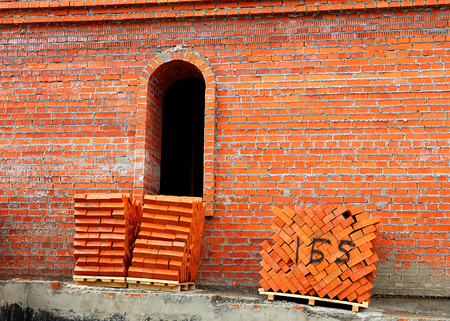 Red bricks on pallets near the wall of the building under construction