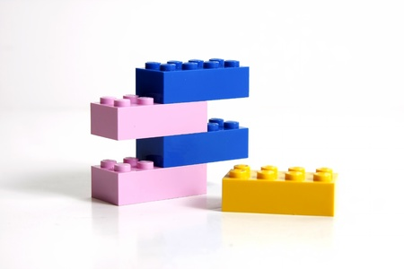 yellow block: One yellow block and a stack of blue and pink ones. Stock Photo