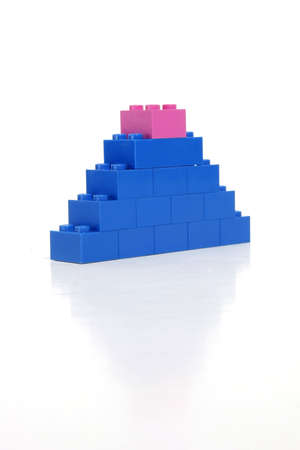 Pink block on top of a blue tower indicates womans strength. Banco de Imagens