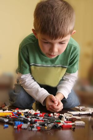 concentrating: Young boy concentrating on building blocks.