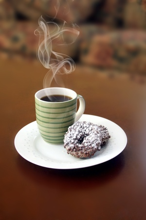 Coffe and donuts on a white plate with steam rising up from the cup. photo