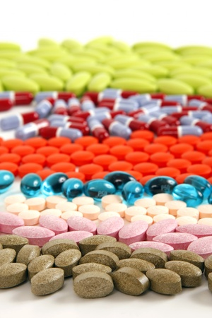 Different colored and shaped pills lined up on a white background.
