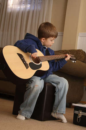 Young Boy playing the guitar during lessons.