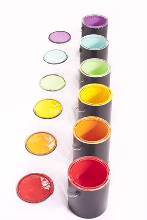Colorful paint cans in a line on a white background photo