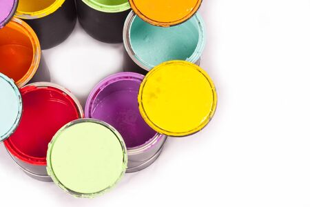 Colorful paint cans in a circle with lids on top cropped on a white background photo