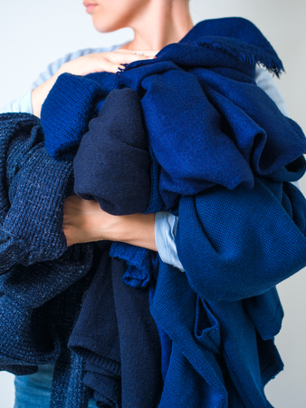 womans hands holding a pile of soft warm cashmere woolen knitting clothes of blue color sweaters. cleaning concept.
