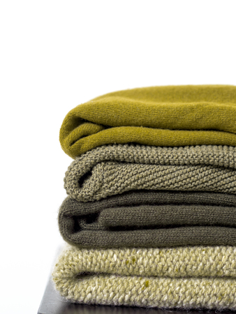 Careful stack of green colors woolen and cashmere sweaters on white background. capsule wardrobe.