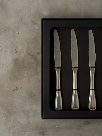 Top view of silver collection of knives in a black box on a gray concrete background