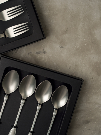Top view of silver collection of knives forks spoons tablespoons and teaspoons in a black box on a gray concrete background