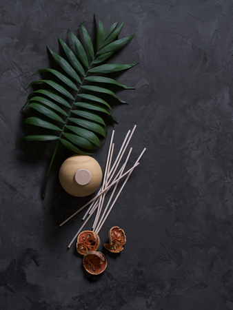 aroma reed diffuser home fragrance with rattan sticks on a black background with palm leaves and shadows.