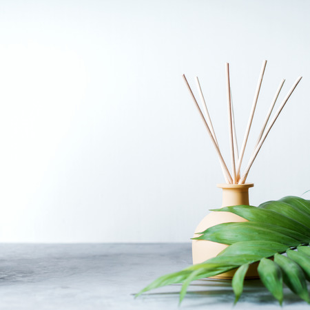 aroma reed diffuser home fragrance with rattan sticks on a light background with palm leaves and shadows. Banco de Imagens