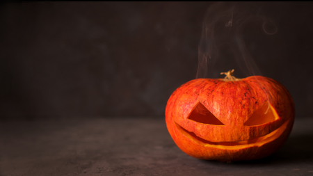 Halloween carved pumpkin head jack lantern with lighting and smoke over black background with copyspace. Halloween celebration. Simple mockup.
