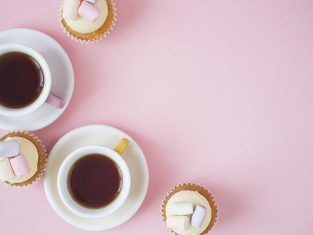 Colorful coffee cups and cupcakes with marshmallows on top on pink background with copy space. Banco de Imagens - 111131039