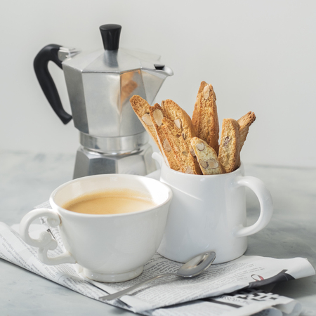 Biscotti (cantuccini) - traditional Italian almond dessert with cup of coffee and Moka coffee pot on newspaper. Still life of simple breakfast.