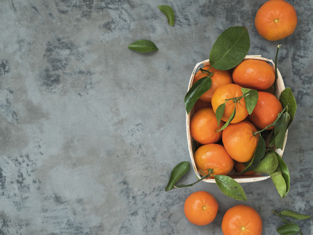 Fresh tangerines with leaves in wooden box on stone surface.