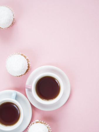 Colorful coffee cups and cupcakes with marshmallows on top on pink background with copy space.