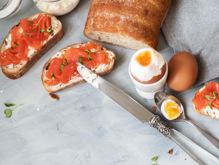 Nature morte au saumon fumé et fromage à la crème sur bruschetta, œufs durs et salade de cresson frais.
