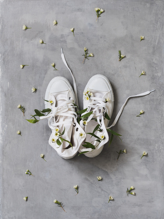 Spring concept of white sneakers with white flowers inside on concrete background.