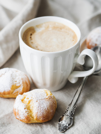 Cakes profiteroles sprinkled with powdered sugar served on white plate with cup of coffee.