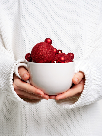 Woman in warm white sweater holding white mug in hands with christmas balls like ice cream. Concept for New year mockup. Stock Photo