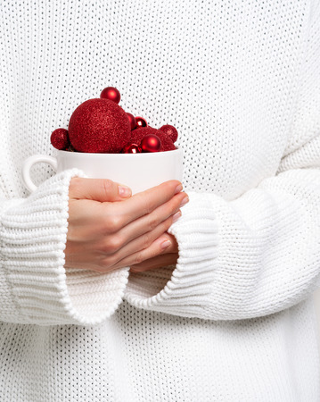 Woman in warm white sweater holding mug with christmas balls like ice cream. Concept for New year mockup.
