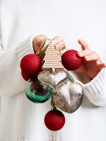 Woman in warm white sweater holding Vintage Christmas tree toy in hands on white background. Concept for New year mockup.