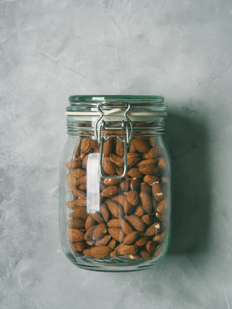 Fresh almonds in a glass jar on a concrete background. Clean eating, vegan, balanced dieting food concept.