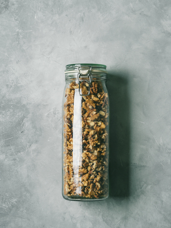 Walnuts in a glass jar on a concrete background. Clean eating, vegan, balanced dieting food concept.