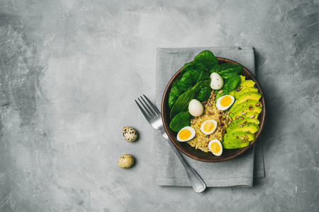 Healthy salad with bulgur, spinach, avocado and quail eggs in a wooden bowl on a concrete background with copy space. Top view.
