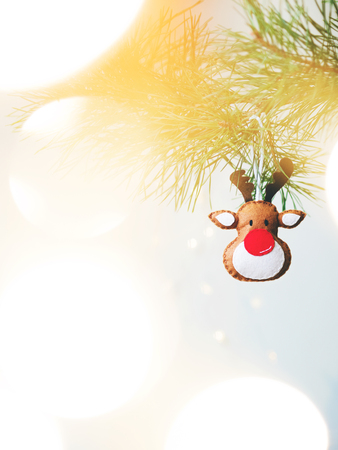 Christmas tree toy Reindeer on a fir branches on light background
