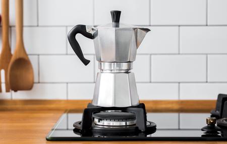 Close-up van Moka-koffiepot op een gasfornuis tegen een muur met witte tegels in keuken met vrije ruimte voor tekst. Scandinavisch design interieur.