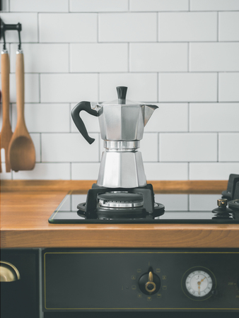 Closeup of Moka coffee pot on a gas stove against a wall with white tiles in kitchen with free space for text. scandinavian design interior.