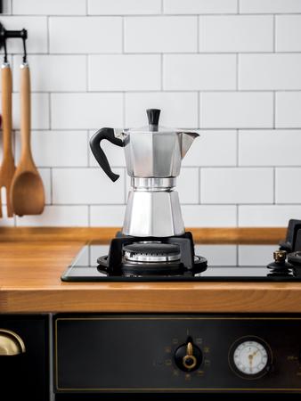 Primo piano della caffettiera Moka su un fornello a gas contro un muro con piastrelle bianche in cucina con spazio libero per il testo. interni di design scandinavo.