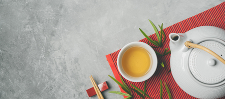 Asian food background with tea set and chopsticks on red bamboo mat on gray stone background. Top view with copy space. Stockfoto