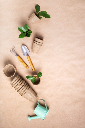 Gardening tools, paper flower pots, watering can on craft paper with copy space. concept of planting Imagens