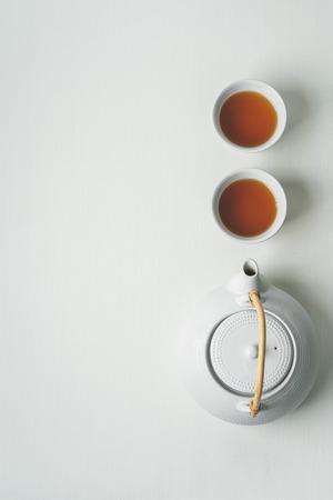 Concepto de té minimalista asiático, dos tazas blancas de té y una tetera vista desde arriba, espacio para un texto sobre fondo de tela blanca.