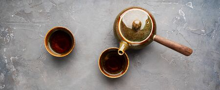 Traditional clay teapot with teapot Flat lay. Long wide banner.Asian food background. 免版税图像