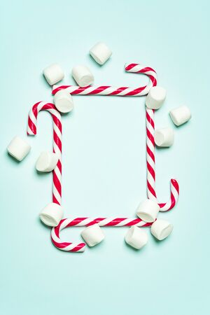 Christmas layout with candy cane and different sizes marshmallows on a turquoise background in the form of square shape. Concept for new year postcard with space for text.
