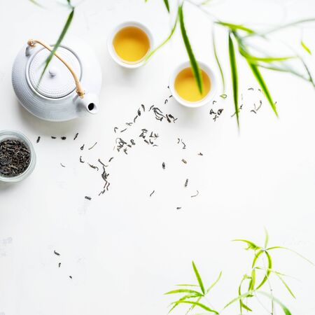 Asian tea concept, two white cups of tea and teapot surrounded with dry green tea  leaves , space for a text on white background. Brewing and Drinking tea.